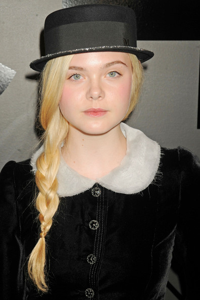 A quick way to add a feminine touch to any boyish cap is to add a lengthy braid like this one worn by Elle Fanning.