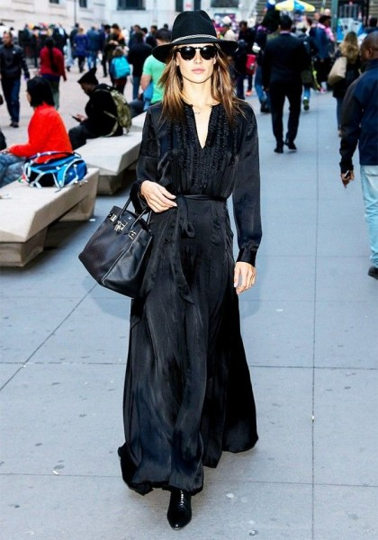 Alessandra Ambrosio wears a silk black maxi dress, a fedora, round sunglasses, boots, and a Birkin bag