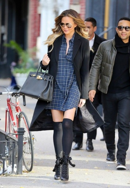 Chrissy Teigen wears a plaid minidress, long black coat, Birkin bag, thigh-high socks, lace-up Chloé boots, and aviator sunglasses