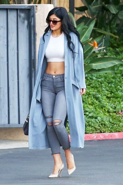 wearing cropped J Brand jeans and a powder blue ASOS duster, accessorized with Jimmy Choo stilettos and abs.