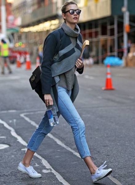 Karlie Kloss wears a gray sweater, striped jacket, cropped jeans, and sneakers.