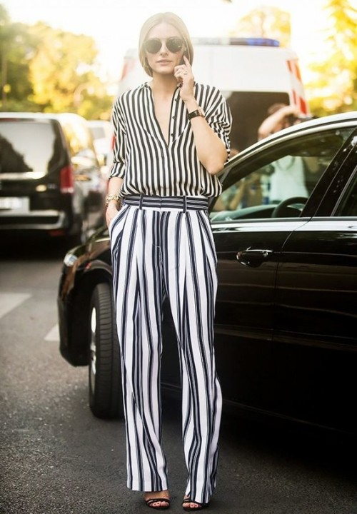Olivia Palermo pairs a striped blouse with striped pants, round sunglasses and black heels.