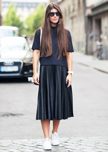 A black t-shirt is worn with a black pleated midi skirt, sneakers, and round sunglasses