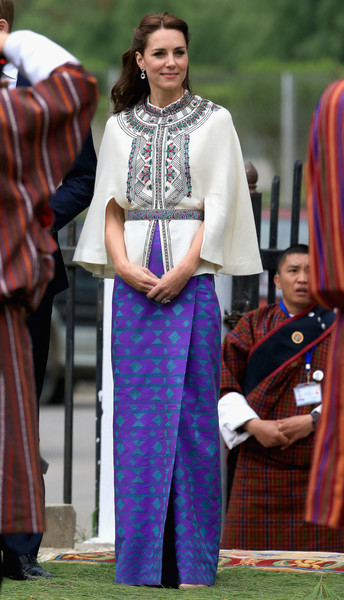 Kate Middleton looked appropriately regal in an embroidered white cape by Paul & Joe while attending a Bhutanese sports demonstration.