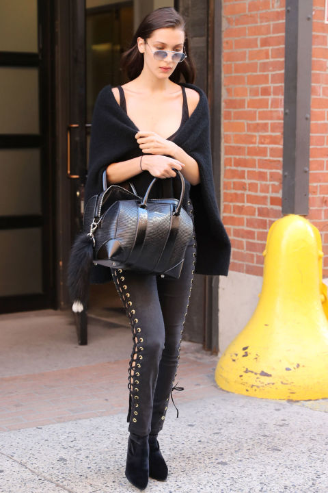 In Velvet boots, black jeans, black wrap and aviators in New York City.
