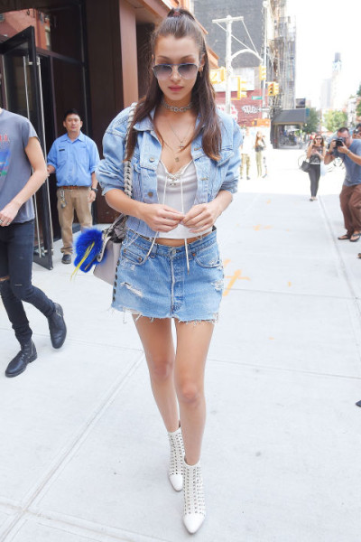 In denim skirt and jacket, white boots, lace up top and aviators in New York City.