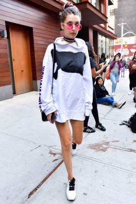 In oversized hooded sweater, choker necklace, statement sunglasses and sneakers on the streets of Manhattan.