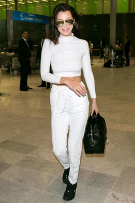 In white turtleneck, white jeans, black bag, sneakers and aviators at Charles-de-Gaulle airport in Paris, France.