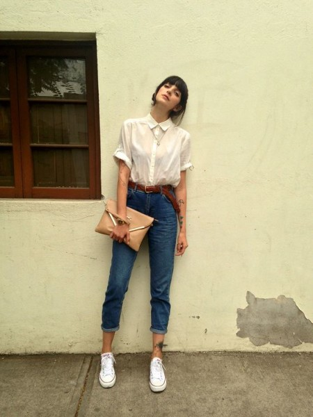 Dark denim mom jeans, white shirt, white sneakers, beige clutch