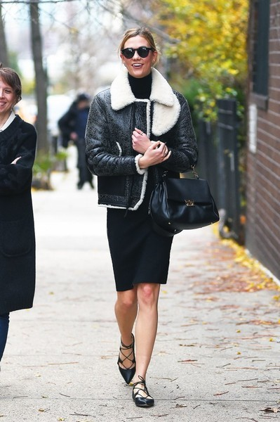 Karlie Kloss beat the New York chill with a distressed leather and shearling flight jacket by Coach that she paired with black Soelae Sunday Somewhere sunglasses.