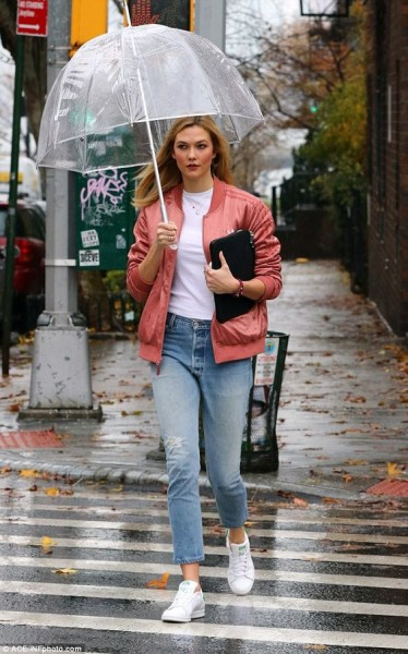 Karlie Kloss braved the rain Wednesday wearing a pretty pink Adidas bomber jacket and coordinating white and green tennis shoes