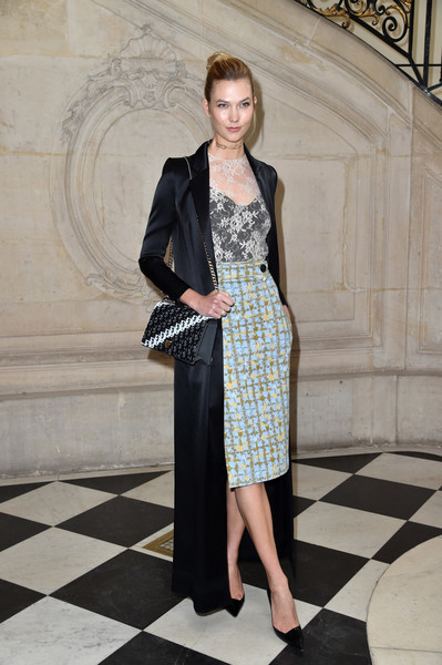 Karlie Kloss made an elegant arrival at the Christian Dior show wearing a floor-length black satin coat.