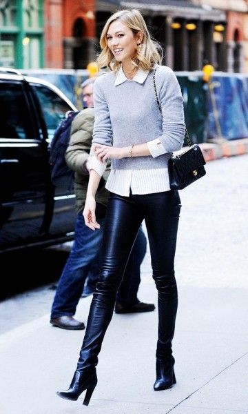 Karlie Kloss steps out in a grey sweater and button-up combo, leather pants and boots.