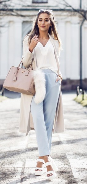 Kenza Zouiten is wearing a creme Ginatricot coat and blouse with baby blue high waisted trousers and white NYL heels