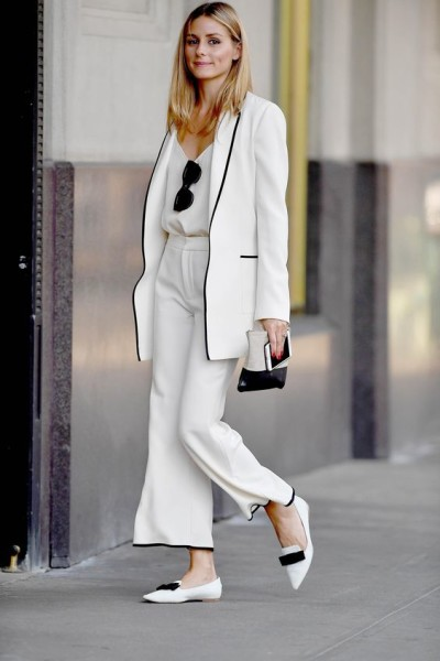 classic ivory suit trimmed in black with Jimmy Choo pointy-toe flats and a Céline zip pouch