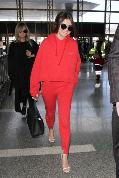 At LAX airport in a Vêtements hoodie, Christian Dior sunglasses, and Jimmy Choo heels.