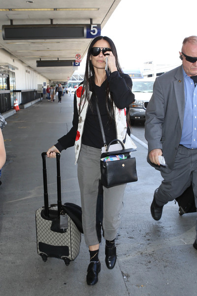 A black leather cross-body tote finished off Demi Moore's airport ensemble.