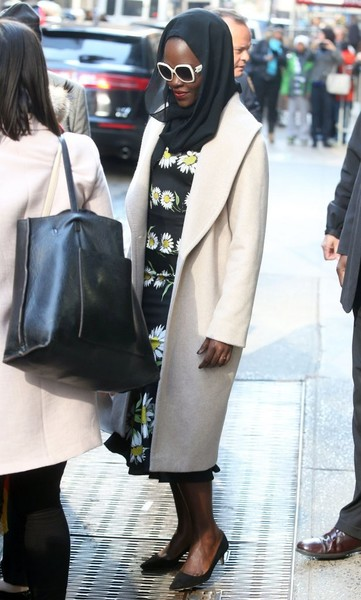 Lupita Nyong'o stopped by 'Good Morning America' wearing a cream-colored wool coat over a floral frock.