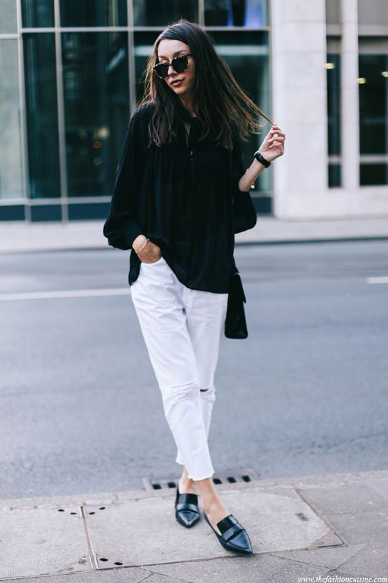 fashion blogger wearing black oversized blouse with white ripped jeans and pointed mango flats