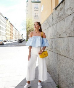 Wearing the classic wide leg pants with an off the shoulder ruffled blouse, white sneakers and bright yellow shoulder bag, completed with bold accessories.