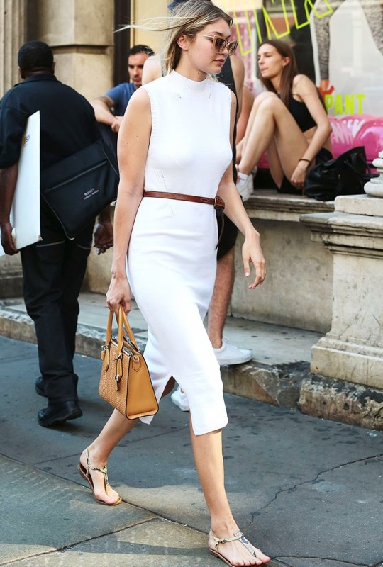 Gigi Hadid wears a white turtleneck bodycon dress with a leather belt, satchel bag, and t-strap sandals
