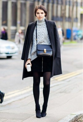 A cable knit sweater is worn with a draped black coat, miniskirt, tights, black heels, and a Céline bag