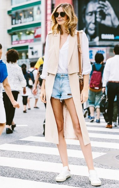 A white blouse is worn with cut-off shorts, sleeveless nude blazer, brown bag, sunglasses and white tennis shoes.