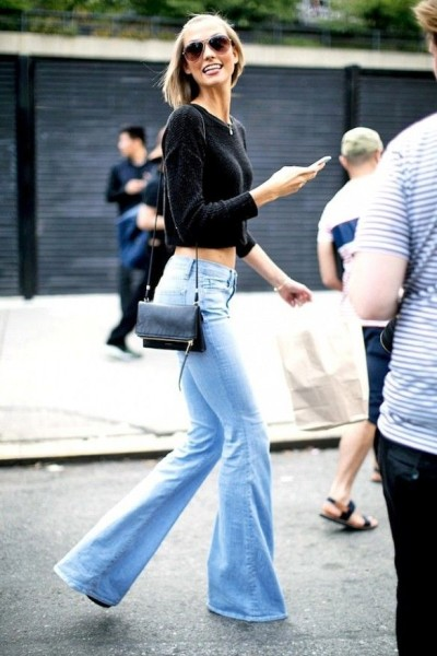Karlie Kloss wears a black cropped sweater with flared jeans, aviators, and a mini bag