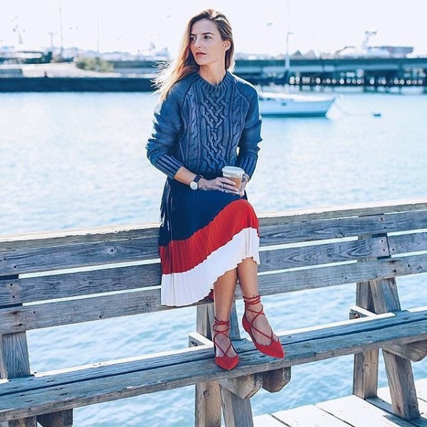 A cable-knit sweater, colorblock skirt, and red lace-up flats