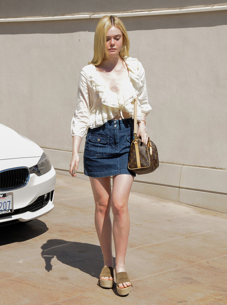 Out in L.A. wearing a denim mini and carrying a Louis Vuitton bag.