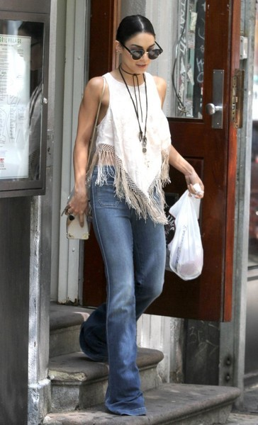 The brunette got into a hippie-chic mood with flared jeans and a fringed white crop-top while out in New York.