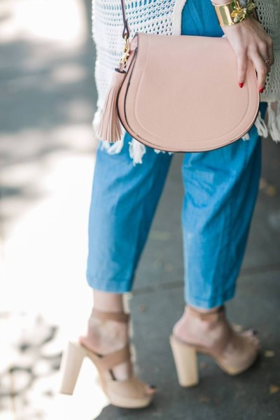a cute pink saddle bag with tassels