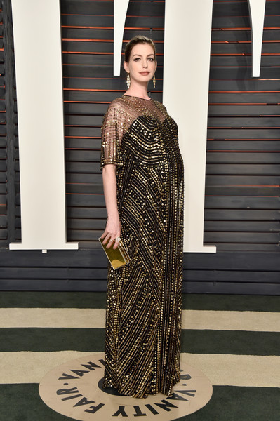 Anne Hathaway dolled up her baby bump in a beaded kaftan by Naeem Khan for the Vanity Fair Oscar party.