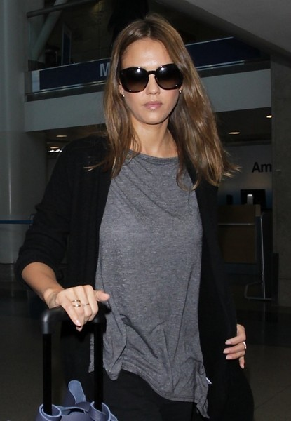Jessica Alba wore a pair of oversized shades to shield her eyes from paparazzi flashbulbs as she made her way through LAX.