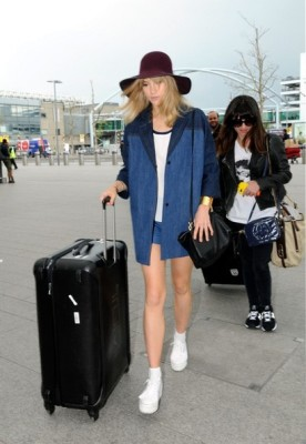 Suki Waterhouse looked very laid-back in a baggy denim jacket layered over a shirt and shorts as she caught a flight out of Heathrow.