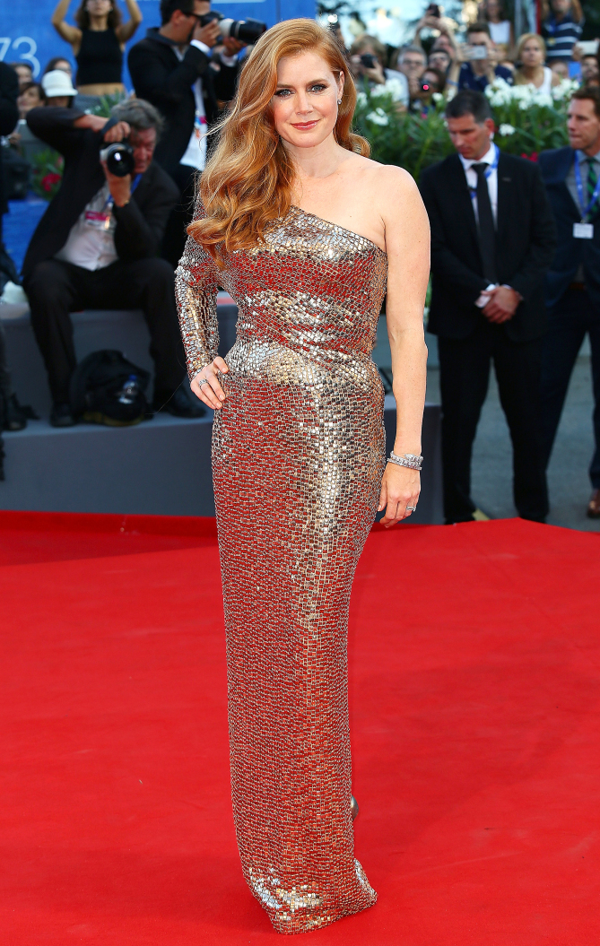 wears a gilded one-shoulder Tom Ford gown with glitzy jewelry and sideswept wave to the Nocturnal Animals premiere.