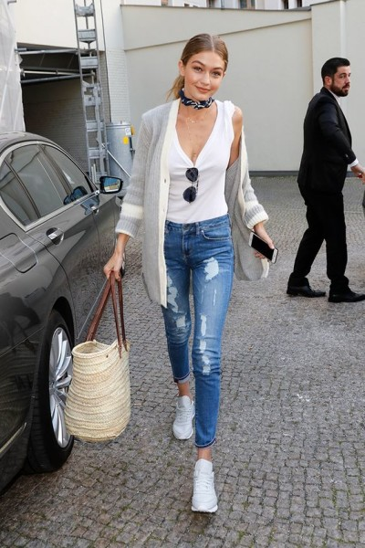 Gigi Hadid looking bodacious in distressed jeans and a simple white tank vest, amped up via a cardigan, bandana choker, Reebok Classics and a basket bag