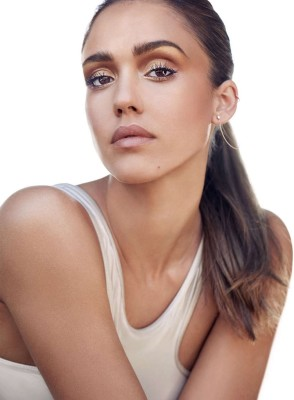 Jessica Alba wears a white tank top with cosmetics from Honest Beauty