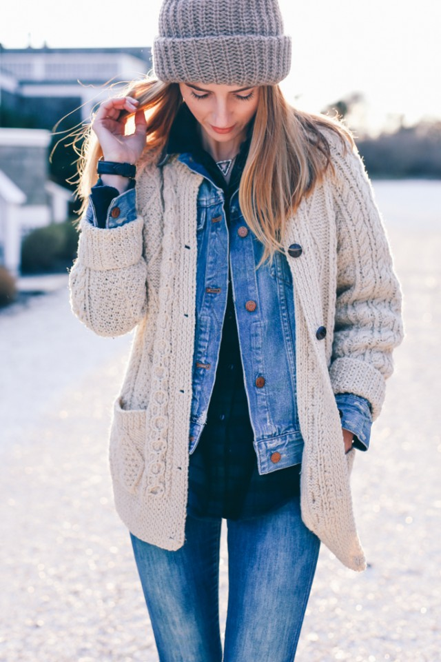 Jess Ann Kirby demonstrates this, pairing a classic Irish knit cardigan with double denim and a plaid button down.