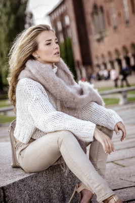 Molly Rustas wears neutral tones, pairing a beige scarf with a cream knit and matching skinnies.