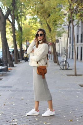 Silvia Zamora wears a grey knit midi skirt with white adidas trainers and a cropped cream knit sweater.