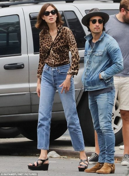 Alexa Chung proves her fashion credentials in an eye-catching leopard print shirt and vintage jeans as she steps out with pals in New York