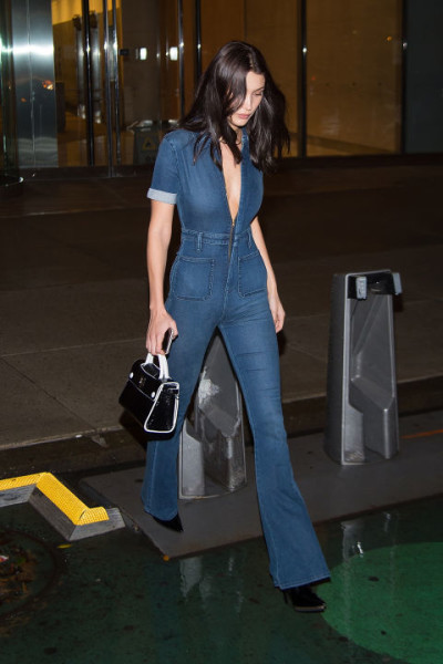 In a v-neck darkwash denim jumpsuit by Second Skin Overalls, a black and white handbag and black pointed-toe booties while out in New York.