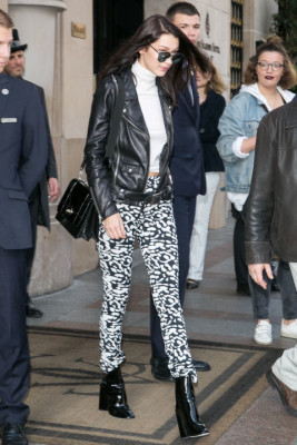 In black and white printed leggings, a white turtleneck, black leather motorcycle jacket, patent leather booties, reflective sunglasses and a structured black handbag while out in Paris.
