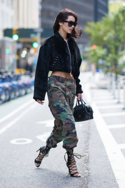 In camo pants, corduroy bomber, lace-up heeled sandals, a black leather satchel and rectangular sunnies leaving the Victoria's Secret offices