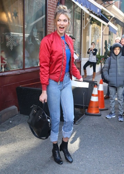 Karlie Kloss cut a colorful figure in a red Unravel bomber jacket layered over a blue shirt while grabbing cupcakes in New York City.