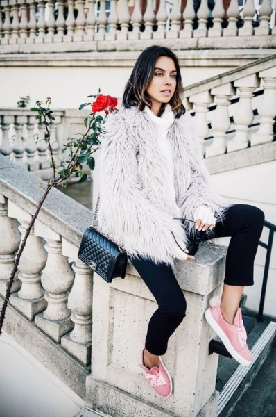 Viva Luxury wears a chunky turtleneck, gray faux-fur coat, skinny jeans, pink sneakers, and a Chanel Boy bag