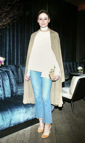 Olivia Palermo looks chic as ever in a choker neck top, cropped flares, and a draped trench coat.
