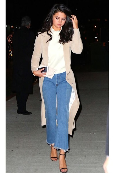 In a Wes Gordon suede camel coat draped over an off-white turtleneck and frayed kick flares for dinner at Nobu in NYC