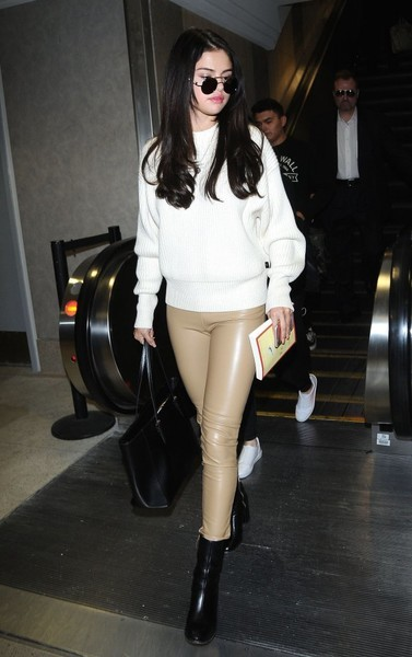 Selena Gomez touched down at LAX looking cozy in a white crewneck sweater.